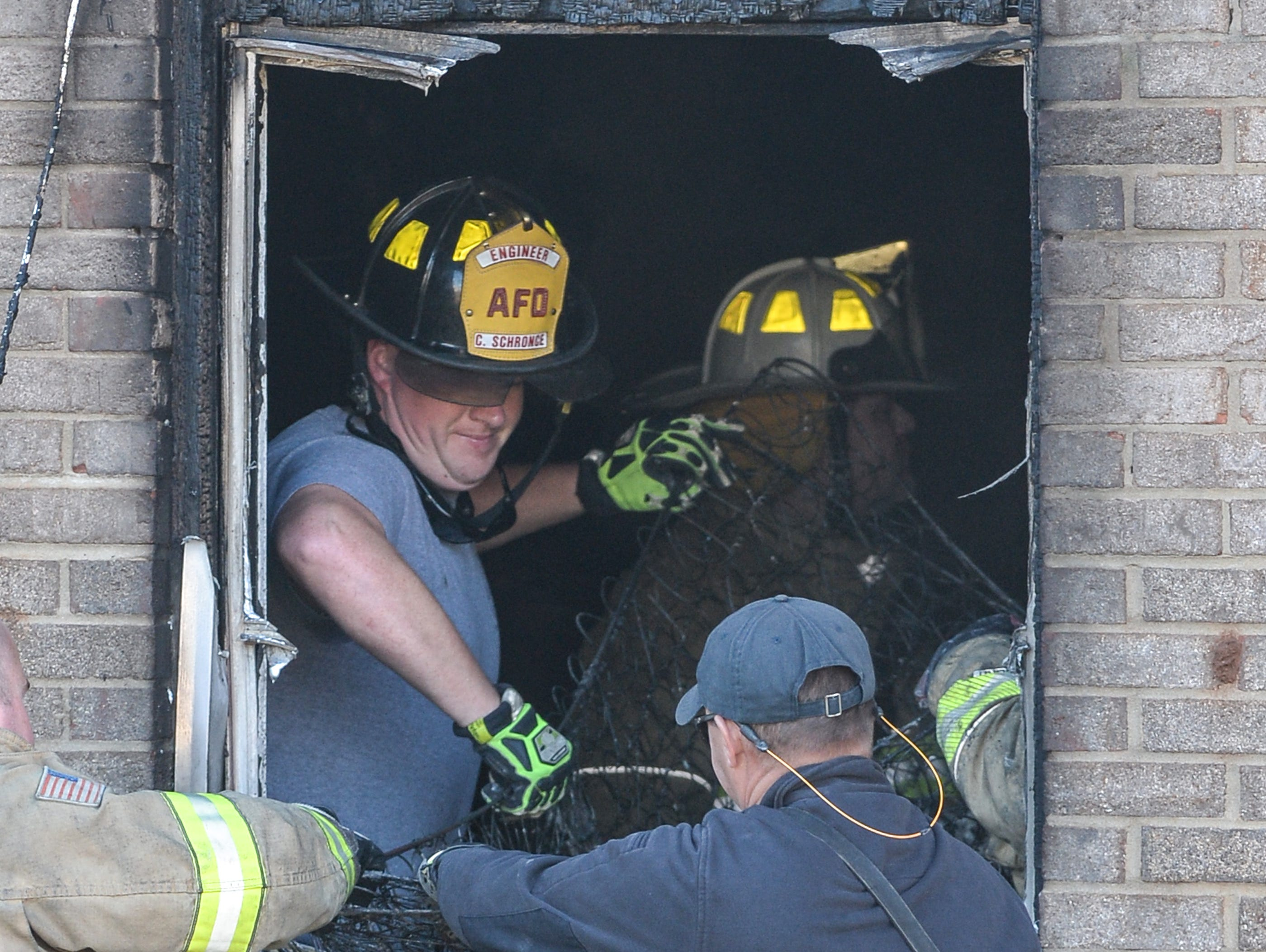 Anderson firemen pull the remains of a box spring mattress out the window of building 8 of the Friendship Court Apartments in Anderson on Tuesday.