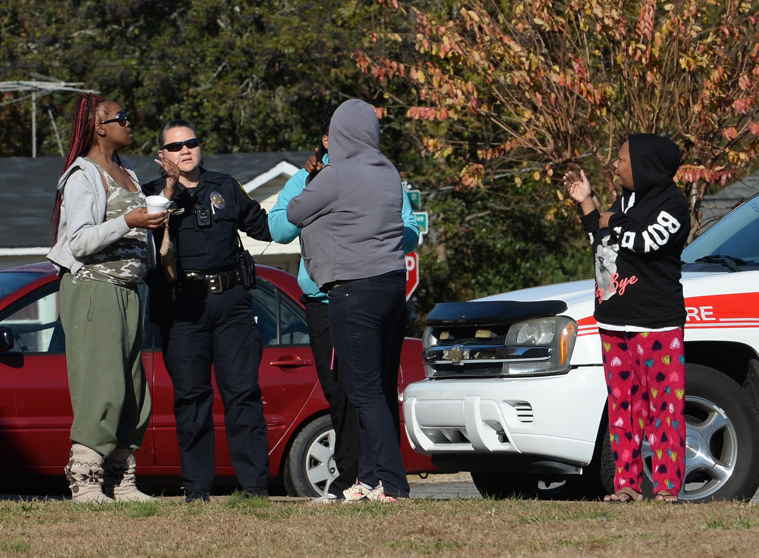 Anderson police talk with bystanders at a fire in building 8 of the Friendship Court Apartments in Anderson on Tuesday.