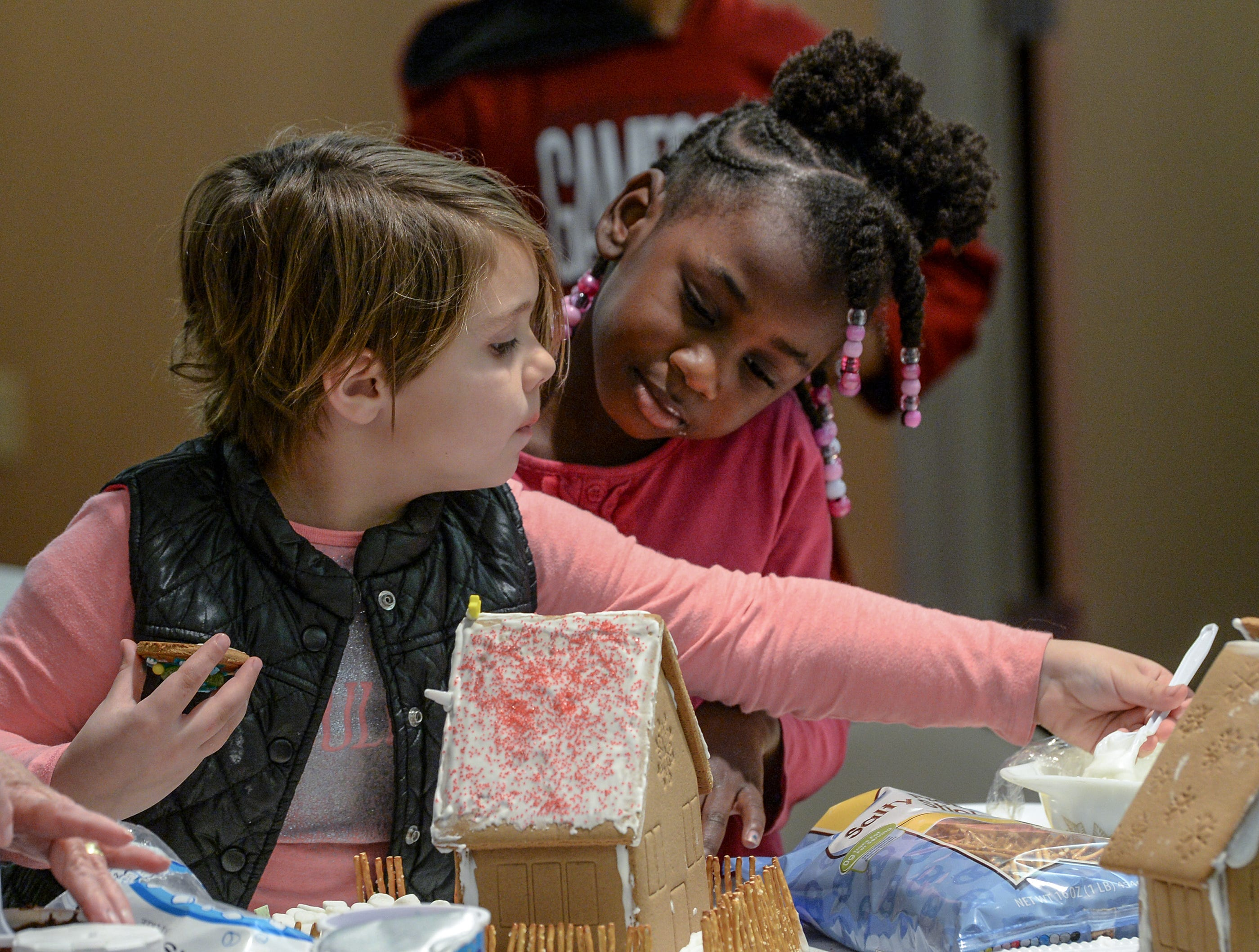 Annabeth Kolb, left, and Sa'Mora Hemphill, right make a  gingerbread house during the Big Brothers Big Sisters of the Upstate gingerbread house decorating party at the Anderson County Museum in Anderson on Tuesday. Older mentors spend six hours or more a month with their little brother or sister, including the group activity with materials donated by local businesses. The group matches up mentors in Anderson, Oconee, and Pickens Counties.
