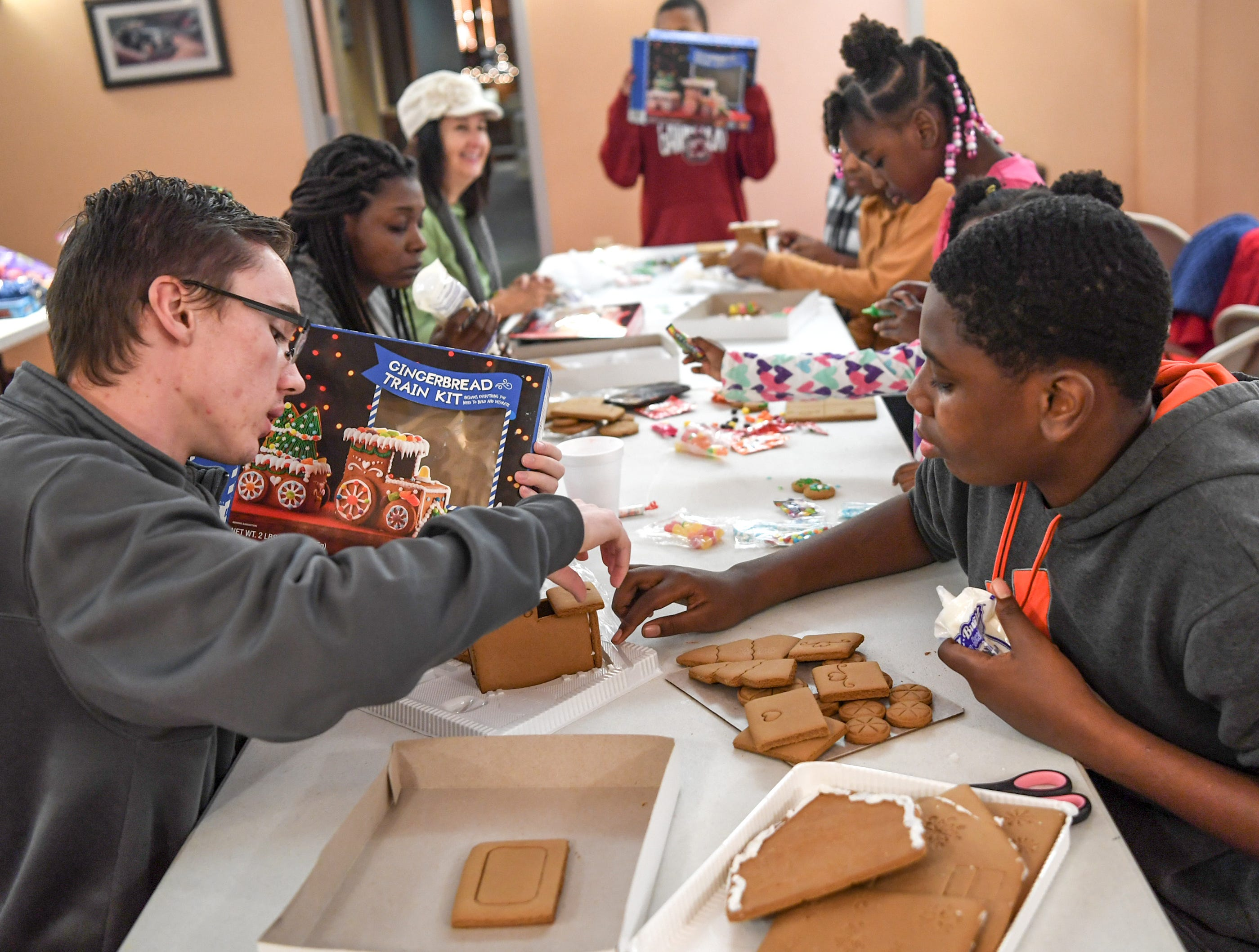 Ryan Null, left, of Williamston, and his little brother Kazianes Hemphill, make their own train shaped gingerbread creation, during the Big Brothers Big Sisters of the Upstate gingerbread house decorating party at the Anderson County Museum in Anderson on Tuesday. Older mentors spend six hours or more a month with their little brother or sister, including the group activity with materials donated by local businesses. The group matches up mentors in Anderson, Oconee, and Pickens Counties.