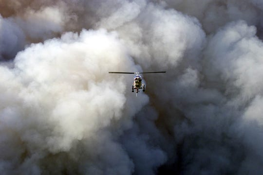 In 2001, a State Forest Fire observation helicopter flies through a large plume of smoke over the Warren Grove Bombing Range.