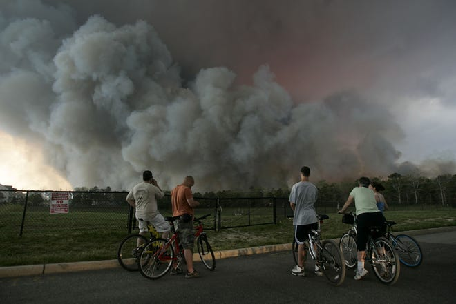 People watch as smoke clouds rise from the Warren Grove fire in Barnegat on May 16, 2007.