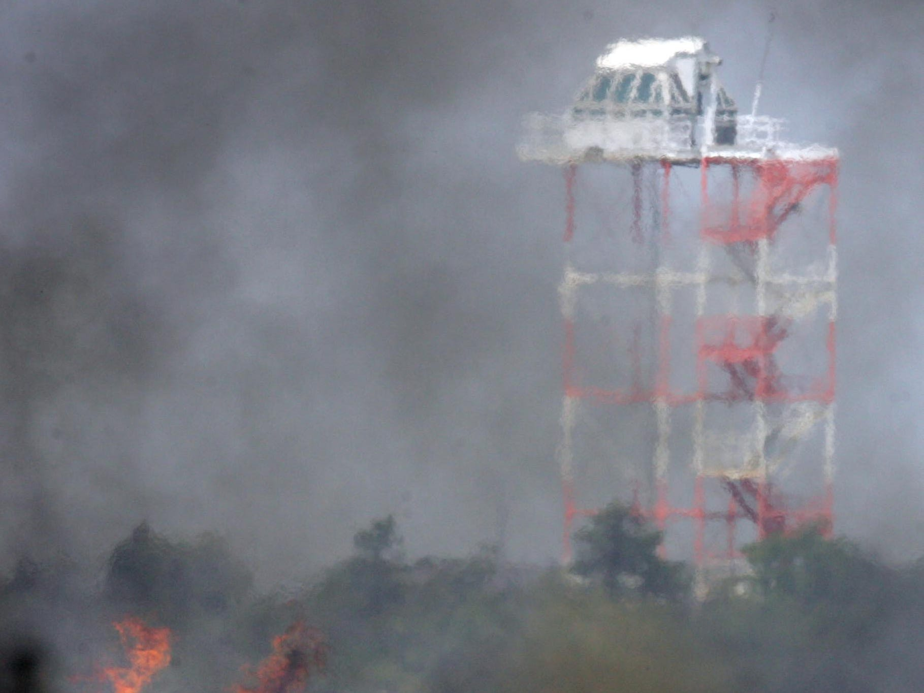An observation tower is seen through smoke during the 2007 fire that started at the Warren Grove Range.