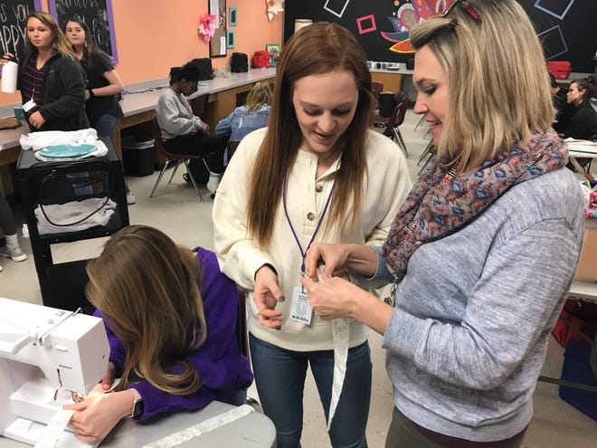 Morgan Morris, center, gets a lesson on making hair scrunchies from Wylie High School teacher Daisy Blair, right. The two, along with Pierson Sanders, sewing more scrunchies at the sewing machine, spent part of their day Tuesday preparing for the second Wylie Bulldog Christmas Market, which runs from 5 to 8 p.m. Thursday.