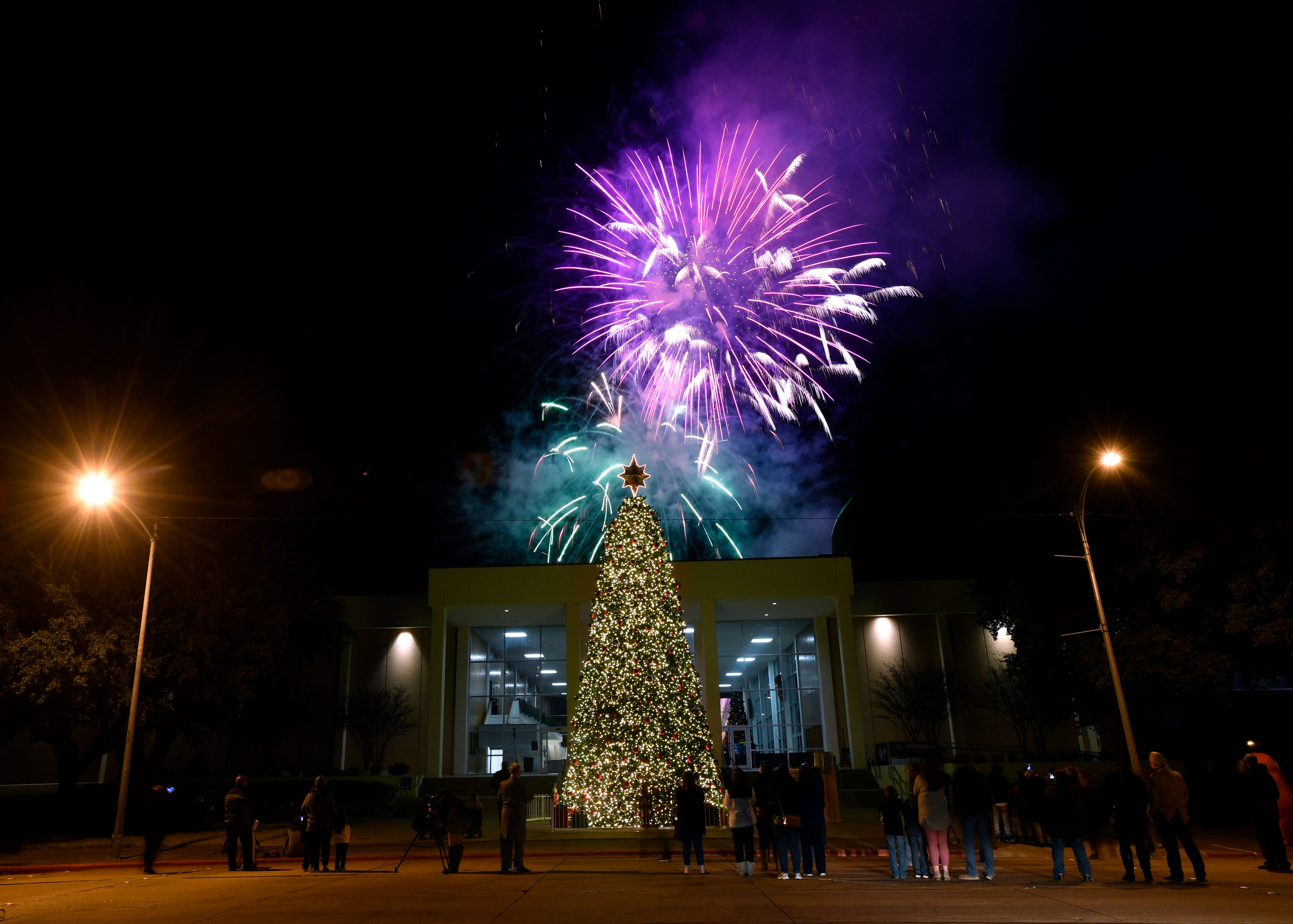 Fireworks explode in the sky behind the Abilene Convention Center Monday Nov. 26, 2018 after the lighting of the city's Christmas tree.