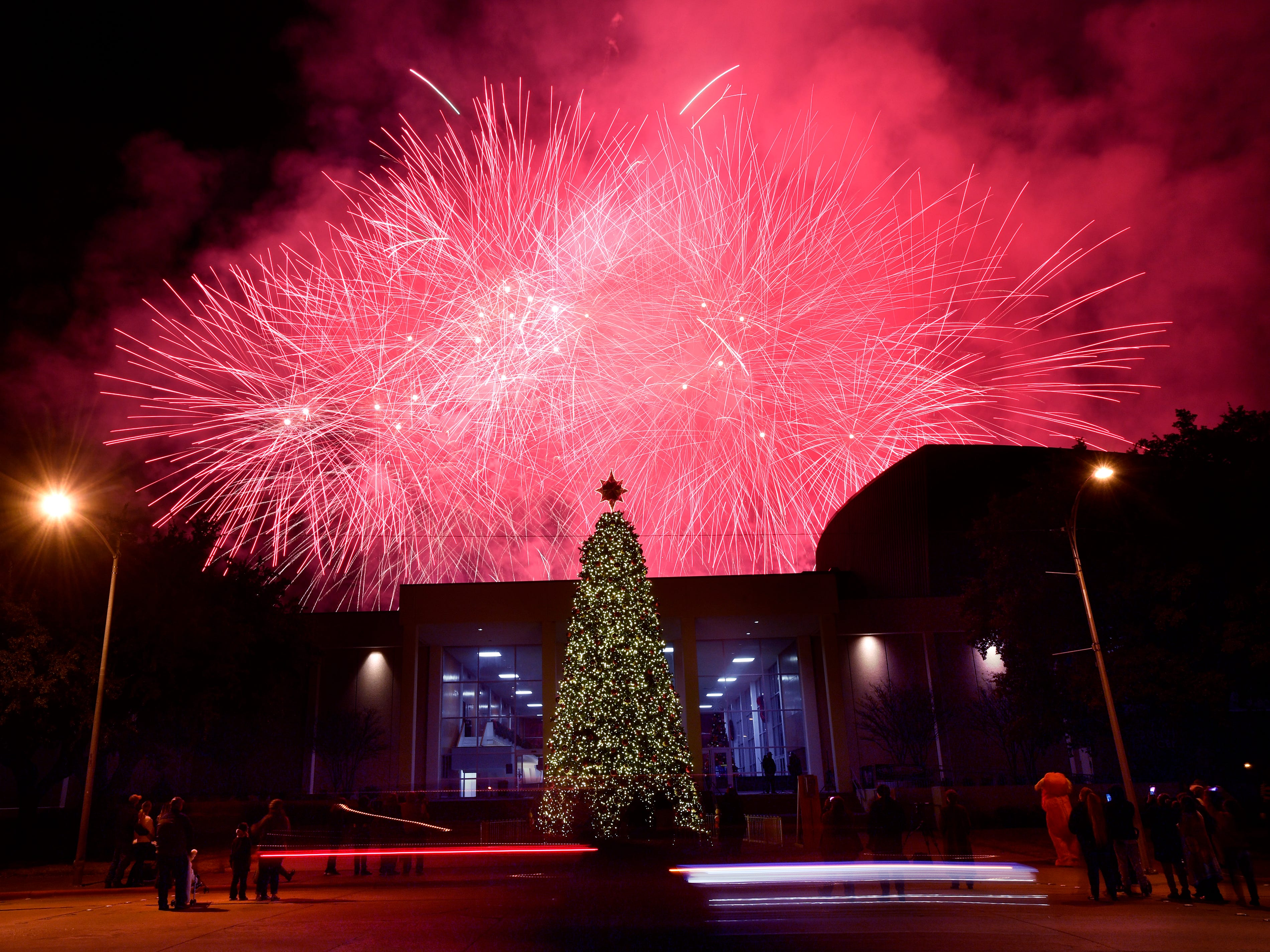 A car is blurred in the foreground as fireworks explode in the sky behind the Abilene Convention Center Monday Nov. 26, 2018 after the lighting of the city's Christmas tree.