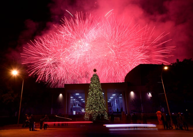 A car is blurred in the foreground as fireworks explode in the sky behind the Abilene Convention Center Monday after the lighting of the city's Christmas tree.