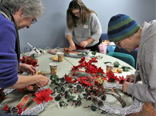 Clockwise from left, Sue Daniels, Ruthie Gaston and Cindy Crane are busy with wreath creations, fortified by small cups of wassail.