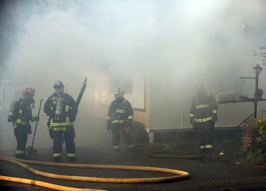 Central Kitsap firefighters are enveloped in smoke as they grab their gear while extinguishing a 2-alarm structure fire at the Country Lane Mobile Home Park in Bremerton on Tuesday, November 27, 2018.