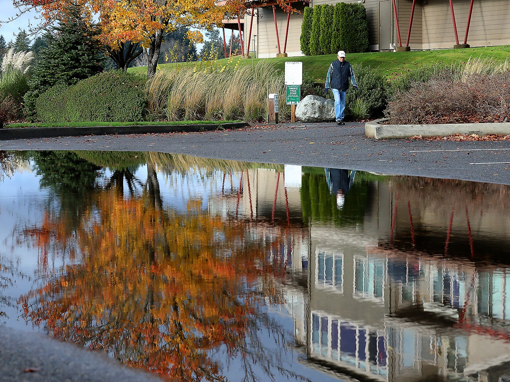 A walker skirts a large puddle reflecting the late Fall season colors at Lions Park in Bremerton on Tuesday, November 27, 2018.