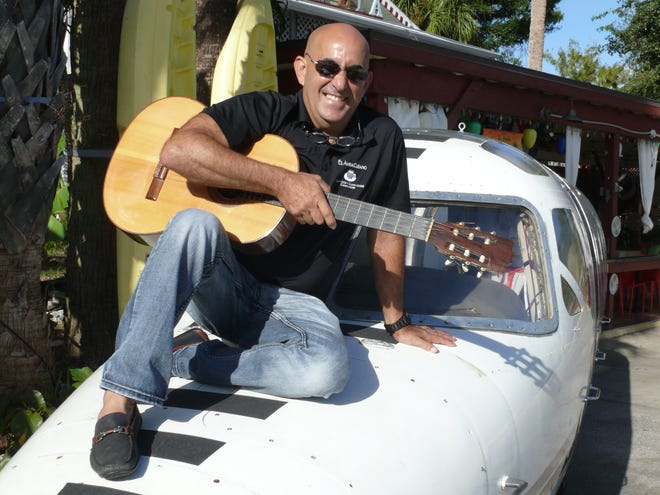 Alfredo Hernandez, owner of El Ambia Cubano in downtown Melbourne, plays his guitar and regales guests with stories.