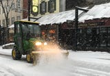A tractor sweeps aside Tuesday morning's snow in downtown Burlington. Produced Nov. 27, 2018.