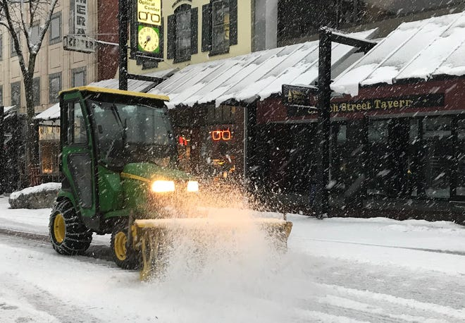 Sweeping Church Street: a small tractor clears fresh snow in downtown Burlington on Tuesday, Nov. 27, 2018.