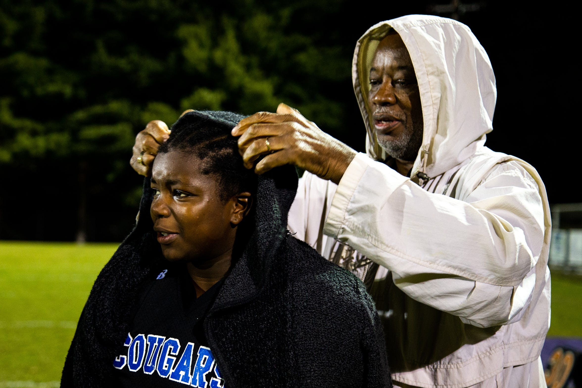 Madisen Bryant's father Joe Bryant covers them with a jacket after the game against the Cowboys at Clarksville High School Thursday, Oct. 18, 2018, in Clarksville, Tenn. This game reunited Ari and Madisen, who took dance classes together when they were younger, but hadn't spoken since.