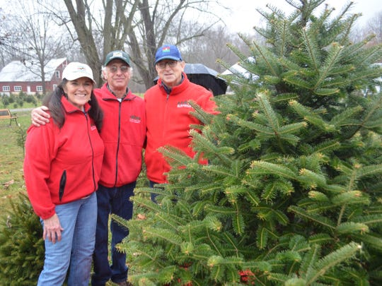 (From left) Kingdom of Car-Lay Christmas Tree Farm owners Layce Gebhard and Carl Paffendorf along with New Jersey Secretary of Agriculture Douglas H. Fisher standing next to the Norway Spruce tree that won the annual contest by the New Jersey Christmas Tree Growers Association.