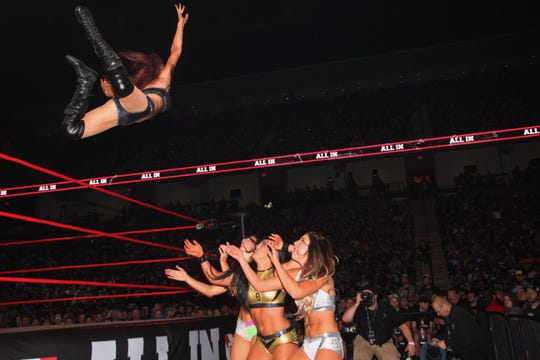 Ashley Simmons Lomberger, known to professional wrestling fans as Madison Rayne, dives out onto Chelsea Green, Tessa Blanchard and Britt Baker during a match at All In, one of the biggest independent wrestling show ever in the United States in September in Chicago. Many wrestling critics said it was one of the best matches on a stacked card.
