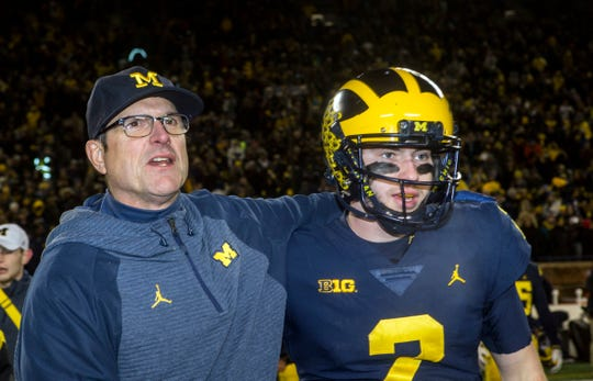 Michigan coach Jim Harbaugh puts an arm around Michigan quarterback Shea Patterson after defeating Indiana 31-20 in Ann Arbor, Nov. 17, 2018.
