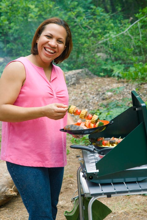 Woman Grilling Kabobs Outdoors