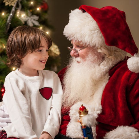 A young boy sits on Santa Claus' lap by a decorated Christmas tree in his living room.