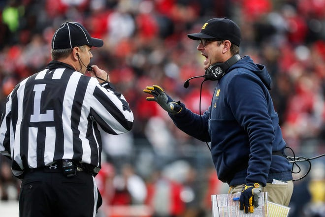 Michigan head coach Jim Harbaugh talks to a referee during the first half against Ohio State at Ohio Stadium in Columbus, Ohio, Saturday, Nov. 24, 2018.