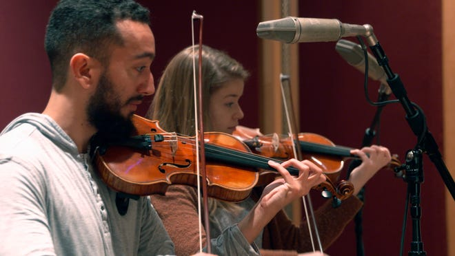 """In this Nov. 7, 2018, photo, student violinistsReuben Kebedeand Dana Johnson perform at a recording session in Ann Arbor, Mich., with Contemporary Directions Ensemble recording """"The Most Beautiful Time of Life,"""" as it's translated from German to English."""