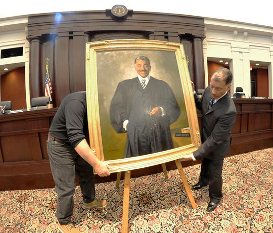 Chief Justice Conrad Mallett, Jr., right, and a court employee move his official portrait after it was presented to the Michigan Supreme Court  in April 2012 in the court's chambers in Lansing.