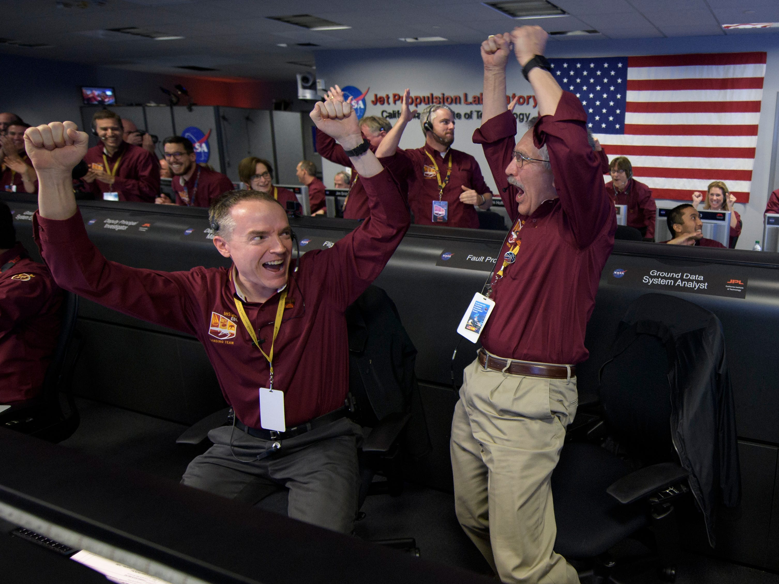 """Mars InSight team members Kris Bruvold, left, and Sandy Krasner react after receiving confirmation that the Mars InSight lander successfully touched down on the surface of Mars, inside the Mission Support Area at NASA's Jet Propulsion Laboratory on November 26, 2018, in Pasadena, California.  InSight, short for Interior Exploration using Seismic Investigations, Geodesy and Heat Transport, is a Mars lander designed to study the """"inner space"""" of Mars: its crust, mantle, and core."""
