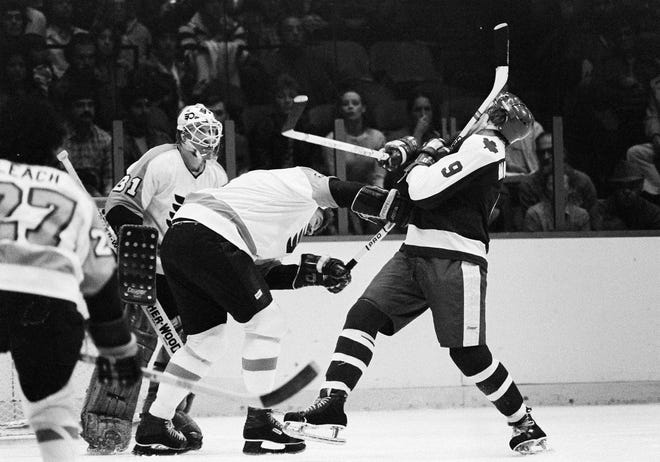 Philadelphia Flyers Bob Dailey, left, gives Toronto Maple Leafs Dan Maloney a shot to the head with his stick early in the game in Philadelphia, Oct. 12, 1980. Dailey and Maloney engaged in a fight after the incident. Maloney, who played for the Detroit Red Wings from 1975-77, died Nov. 19 in his hometown of Barrie, Ontario. He was 69.