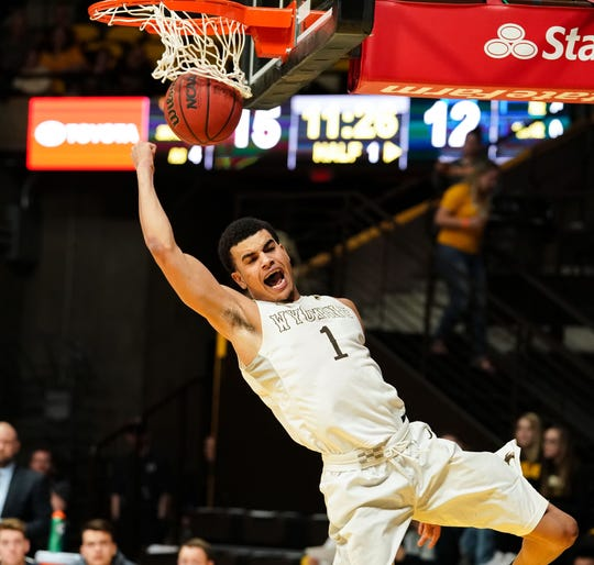 Feb 7, 2018; Laramie, WY, USA; Wyoming Cowboys guard Justin James (1) dunks the ball against the Utah State Aggies during the first half at Arena-Auditorium.