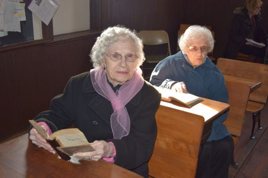 Margaret Steindam, 100, left, and her sister Monica Steindam, 101, sit in desks similar to ones they used while attending this one room schoolhouse as children.