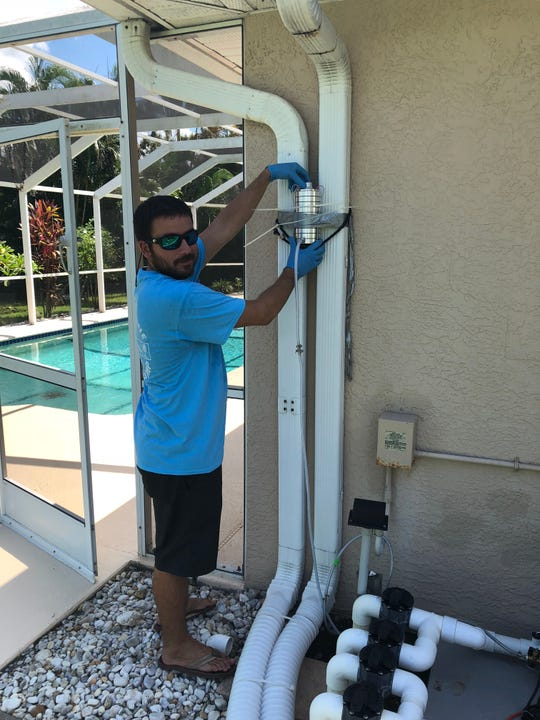 Florida Gulf Coast University graduate student Adam Catasus installs an algae air-sampling pump outside a Cape Coral home.
