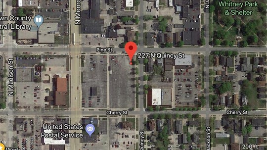 A developer has proposed converting the former Associated Bank parking lot into a mixed-use development that includes apartments, townhouses and a downtown grocery store. The site is bounded by Quincy, Pine and Cherry streets and Monroe Avenue.