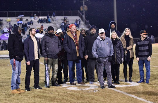 Former boys basketball coach Jeff Neely, front, is joined by family members and former players while being inducted in the Greer High School Ring of Honor Friday night at Dooley Field.