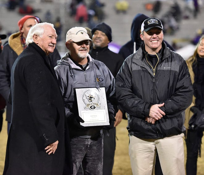 Former boys basketball coach Jeff Neely, center, who became the 17th member of the Greer High School Ring of Honor, is joined by Steve Brown, left, one of the inaugural inductees, and school principal Justin Ludley during a ceremony at Dooley Field Friday night.