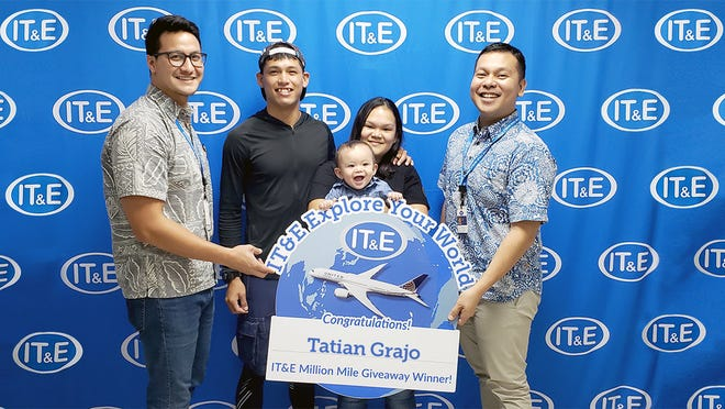 Chris Duenas, IT&E prepaid product specialist and Danny Daniel, senior manager of brand and public relations, IT&E, present Tatian Grajo and his family with 5,000 United MileagePlus miles won through the final social media contest of the IT&E Explore Your World Million Mile Giveaway.