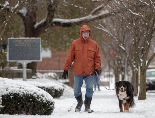 Tom Hartmann, Indianapolis, walks his dog Lucy as light to moderate snow falls throughout central Indiana, Indianapolis, Tuesday, Nov. 27, 2018. Rain is expected to fall on Thursday.