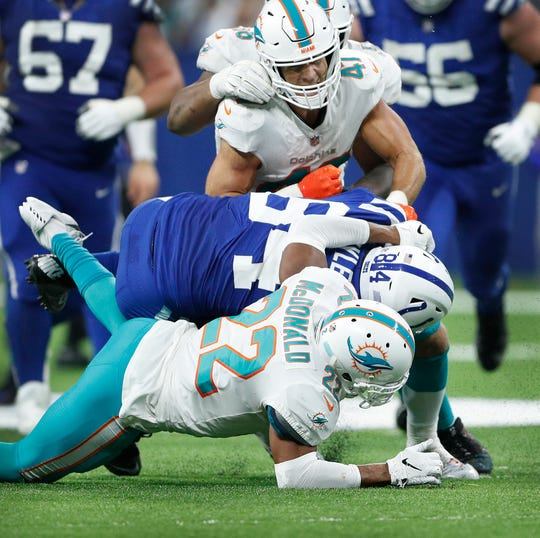 Indianapolis Colts tight end Jack Doyle (84) is hit by Miami Dolphins safety T.J. McDonald (22) and linebacker Kiko Alonso (47) in the fourth quarter of their game at Lucas Oil Stadium on Sunday, Nov. 25, 2018. Doyle suffered a season-ending kidney injury on this play. The Colts defeated the Dolphins 27-24.