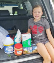 Makayla Southerland poses with her donations for the Humane Society for Hamilton County.