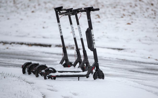 Four Bird scooters sit in fallen snow on a day of light to moderate snowfall throughout central Indiana, Indianapolis, Tuesday, Nov. 27, 2018. Rain is expected to fall on Thursday.