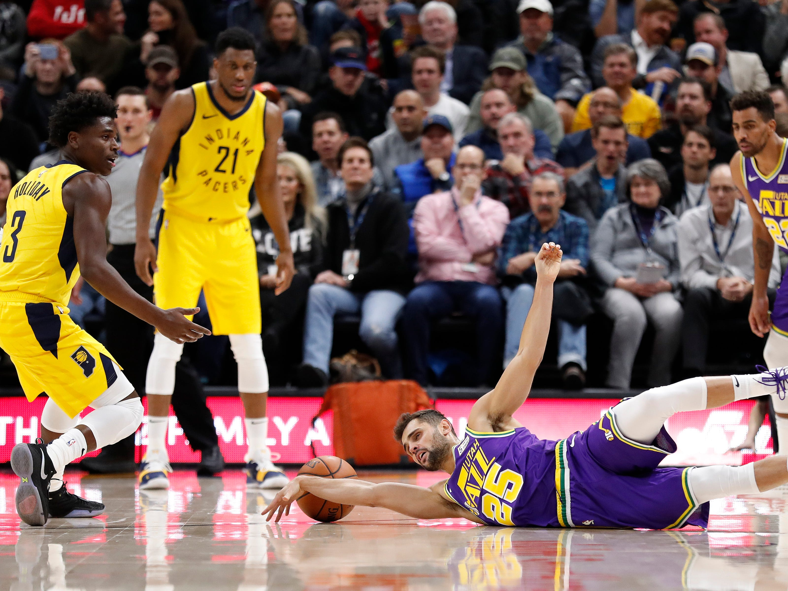 Utah Jazz guard Raul Neto (25) dives for the ball in front of Indiana Pacers guard Aaron Holiday (3) in the second half at Vivint Smart Home Arena.