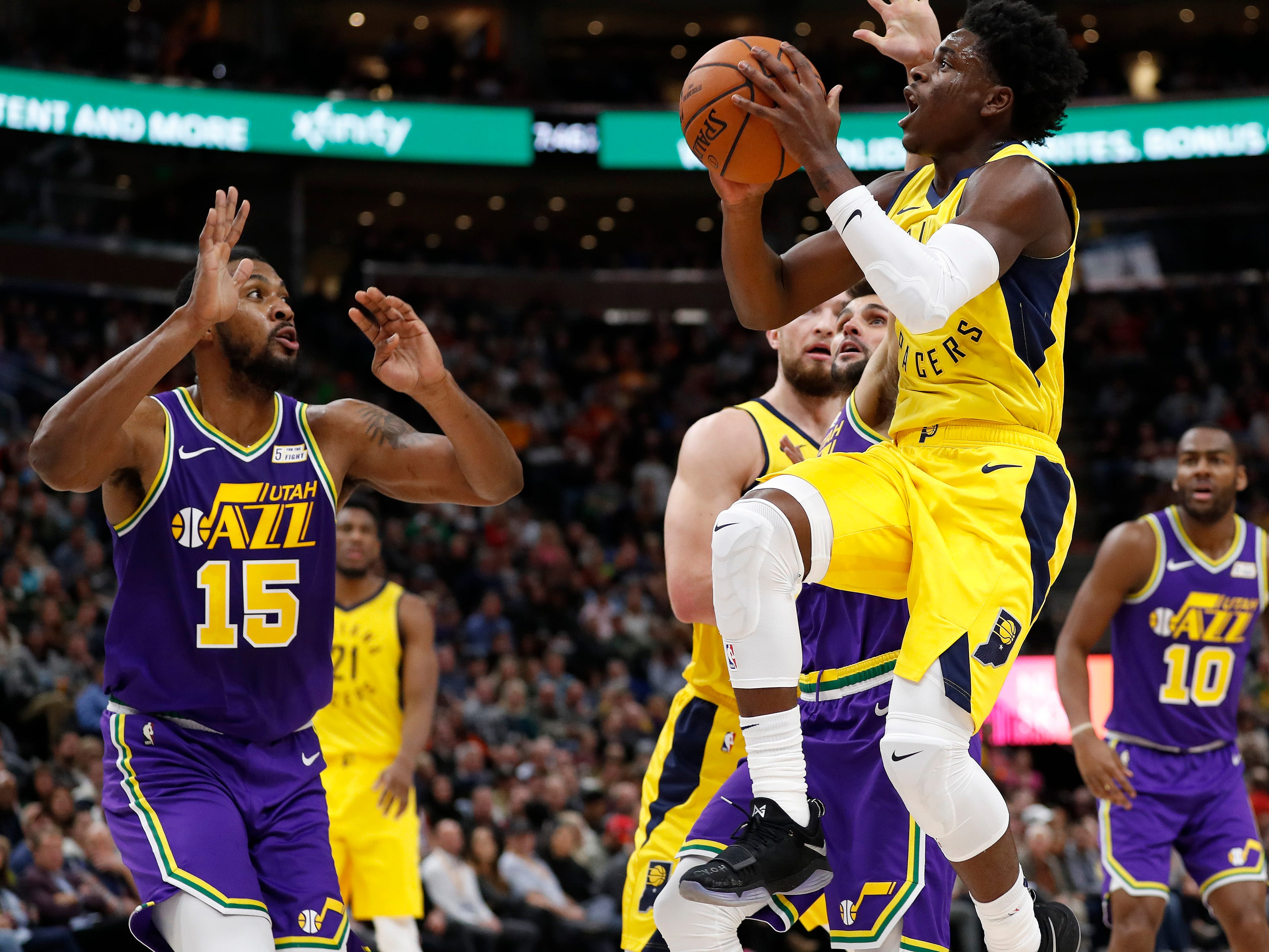 Nov 26, 2018; Salt Lake City, UT, USA; Indiana Pacers guard Aaron Holiday (3) drives to the hoop against Utah Jazz forward Derrick Favors (15) and guard Raul Neto (25) in the second quarter at Vivint Smart Home Arena.