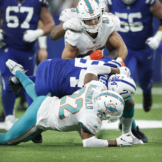 Indianapolis Colts tight end Jack Doyle (84) was hit by Miami Dolphins safety T.J. McDonald (22) and linebacker Kiko Alonso (47) in the fourth quarter of their game at Lucas Oil Stadium on Sunday. Doyle signaled he needed to come out of the game after this play.