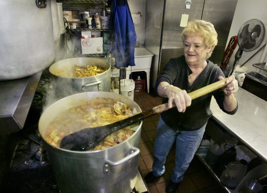 Betty Kassing, manager of John's Famous Stew restaurant), stirs a five-gallon batch of the trademark stew in the kitchen of the restaurant at 1146 Kentucky Ave. A second pot stews on the burner next to it. A husband of one of the restaurant's cooks made the stirring paddle. Meat and spices are mixed in when the stew, which takes three hours to cook, is half finished.
