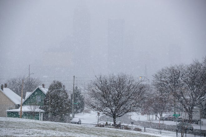 Downtown high rise buildings are barely visible from the east side of downtown during a moderate snowfall throughout central Indiana, Indianapolis, Tuesday, Nov. 27, 2018. Rain is expected to fall on Thursday.