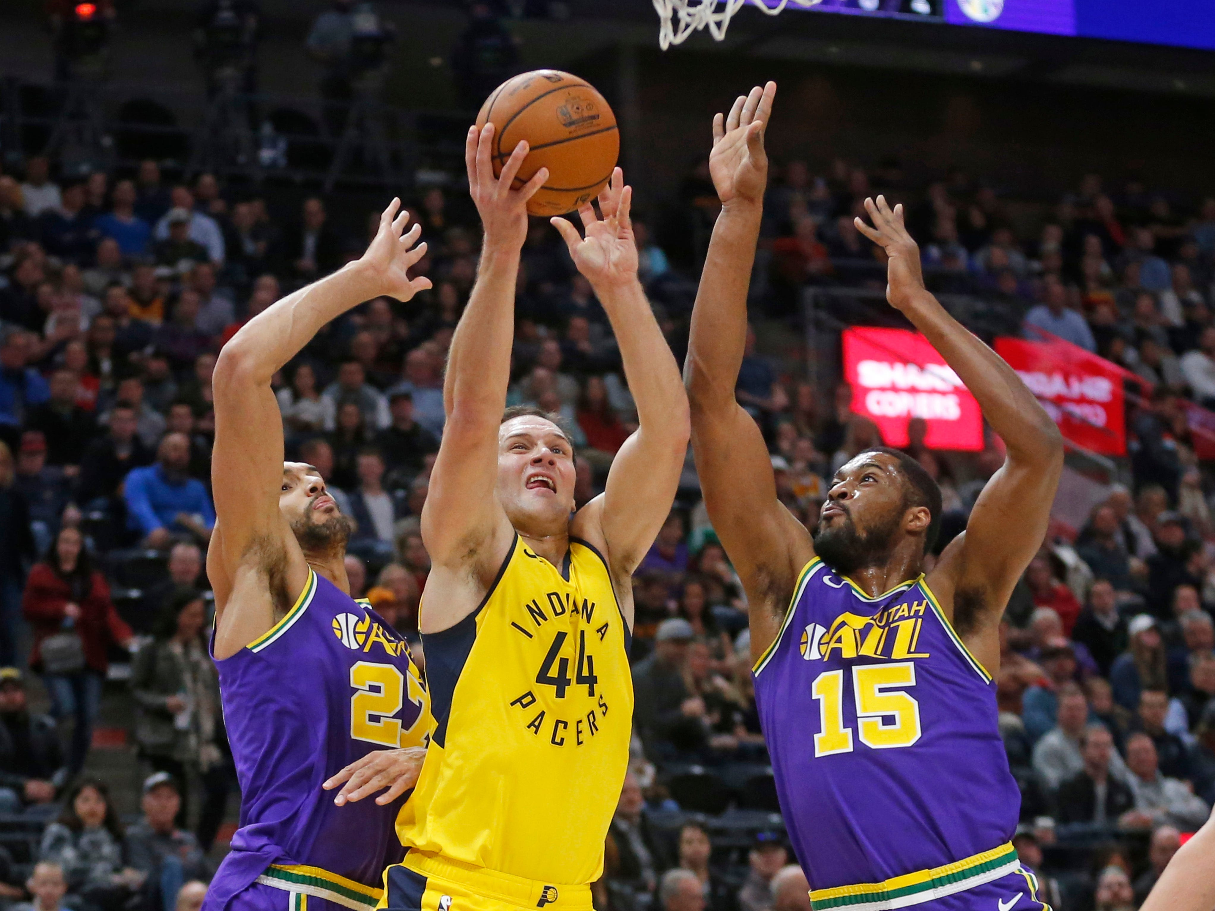 Indiana Pacers forward Bojan Bogdanovic (44) shoots as Utah Jazz's Rudy Gobert (27) and Derrick Favors (15) defend in the first half during an NBA basketball game Monday Nov. 26, 2018, in Salt Lake City.