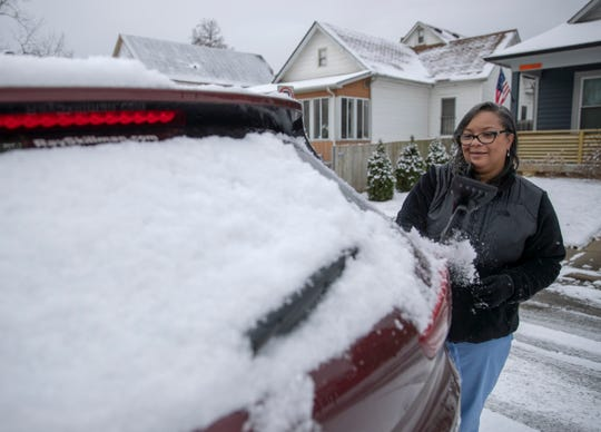 Dana Kirtz, Indianapolis, removes snow from her car before heading to work as light to moderate snow falls throughout central Indiana, Indianapolis, Tuesday, Nov. 27, 2018. Rain is expected to fall on Thursday.