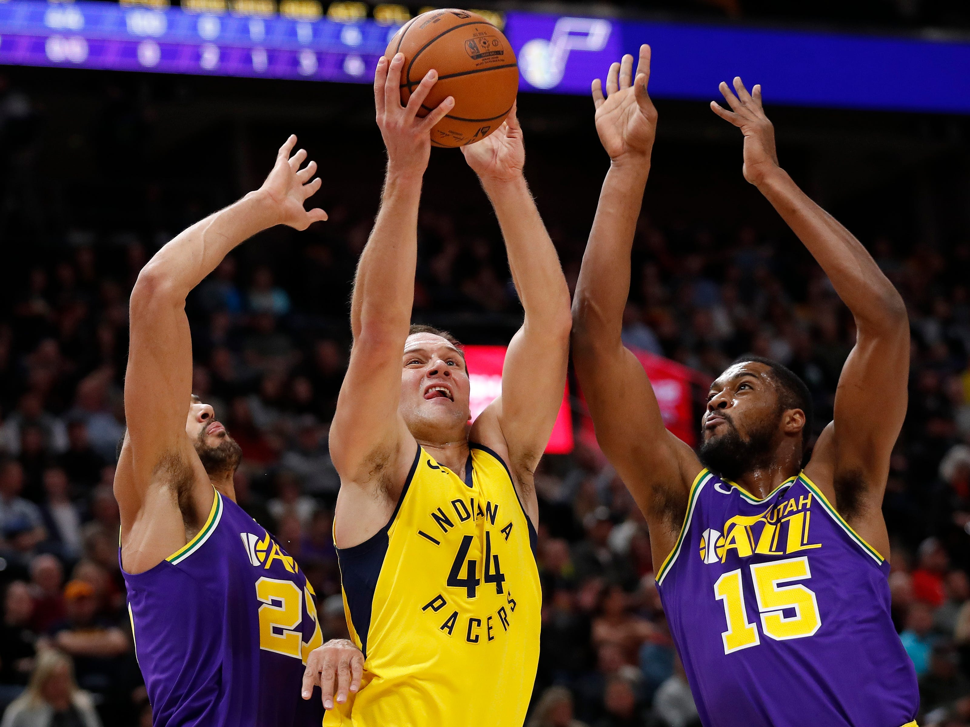 Indiana Pacers forward Bojan Bogdanovic (44) shoots against Utah Jazz center Rudy Gobert (27) and Utah Jazz forward Derrick Favors (15) in the first quarter at Vivint Smart Home Arena.