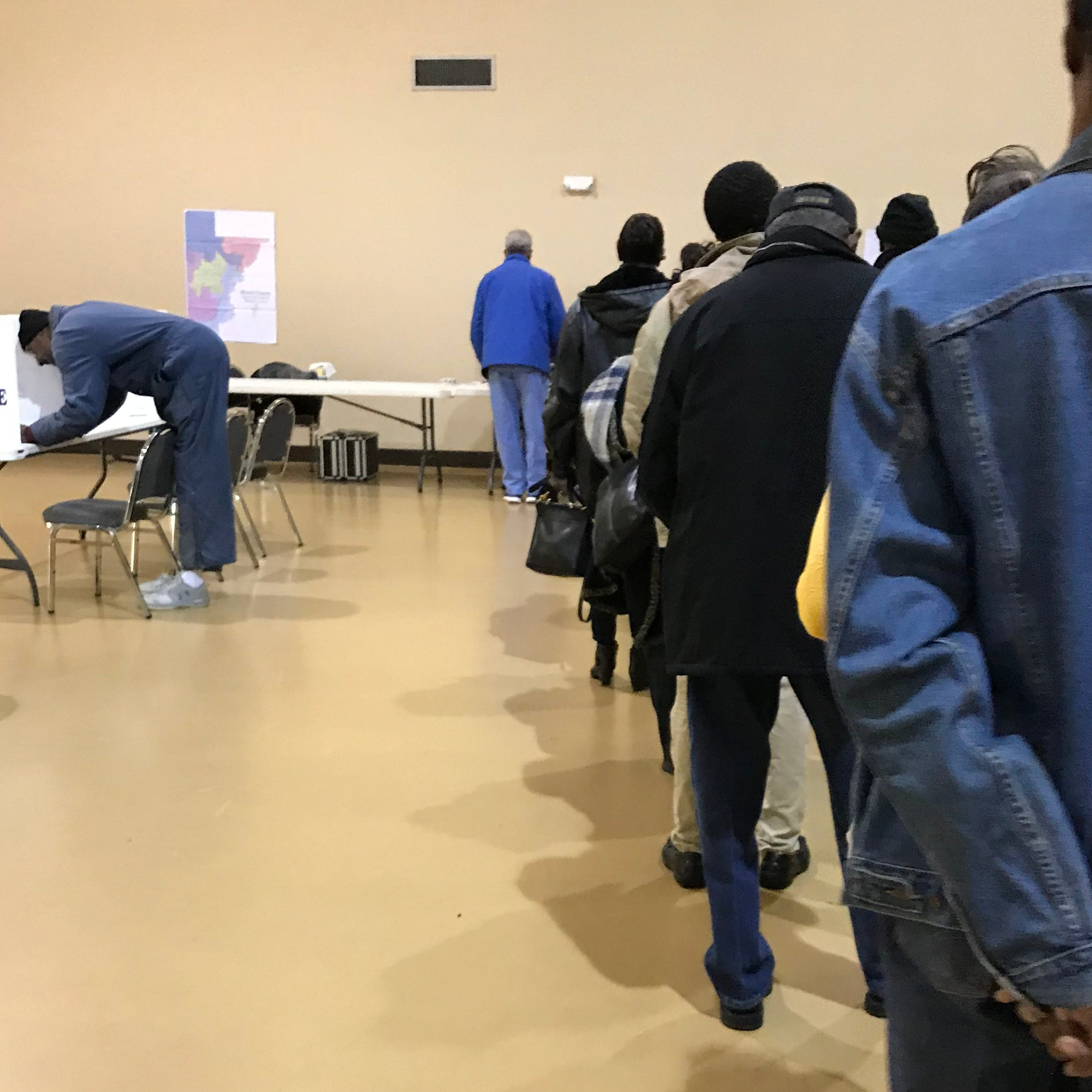 Voters stand in line at the Hanging Moss Road Church of Christ on Tuesday for a runoff election.