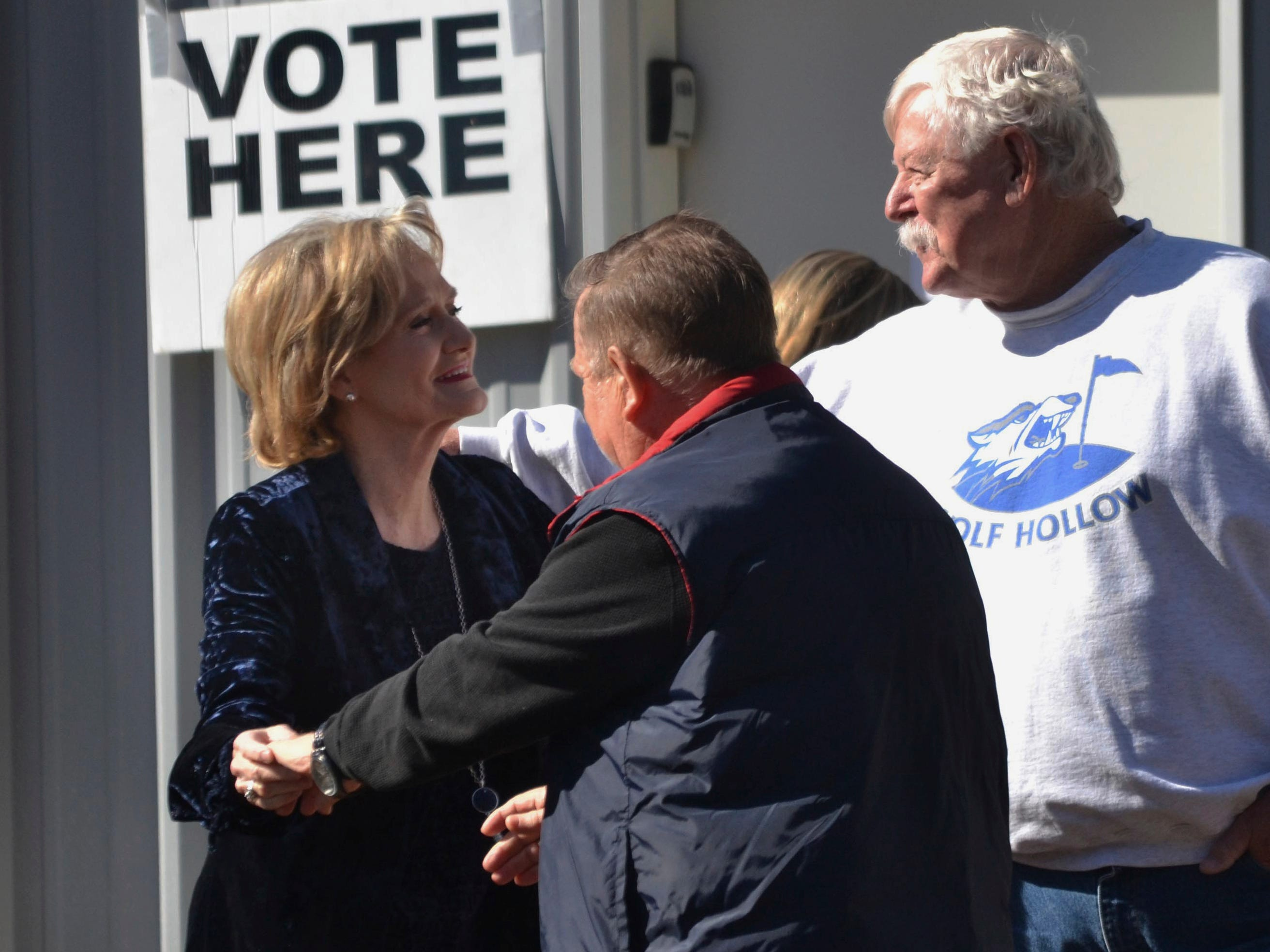 Appointed Republican U.S. Sen. Cindy Hyde-Smith, center, greets neighbors at her Brookhaven, Miss., precinct after voting Tuesday, Nov. 27, 2018, in her runoff race against Democrat Mike Espy.