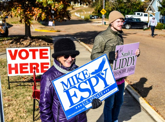 Susan Fino, left, holds a sign for U.S. Senate candidate Mike Espy and Logan Liddy holds one for Susan Liddy, a candidate for judge in the Chancery Court, District 18, Place 1 race at the Oxford Community Center in Oxford, Miss. on Tuesday, November 27, 2018. Mississippians are casting their ballots in runoff elections, including a U.S. Senate race pitting Republican Cindy Hyde-Smith against Democrat Mike Espy.